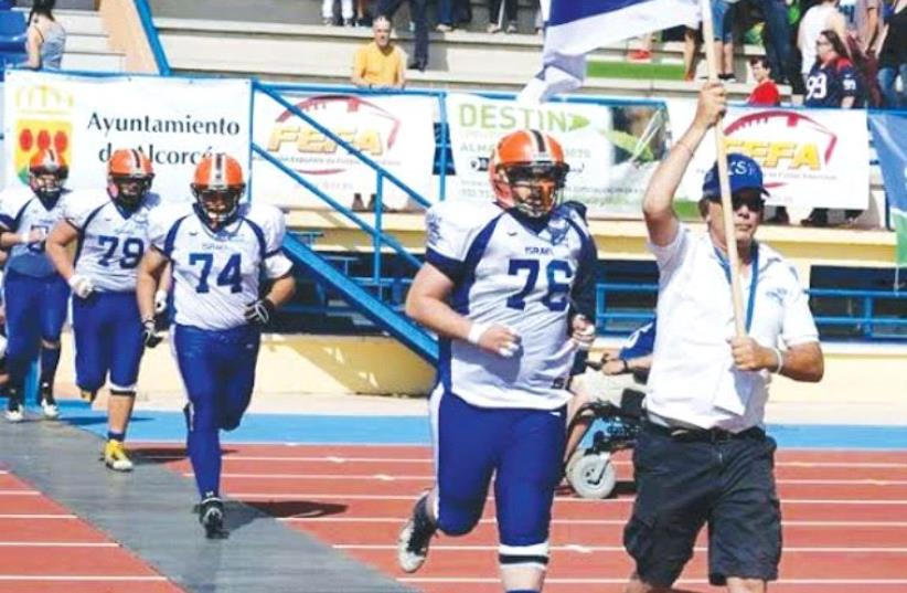 AMERICAN FOOTBALL IN ISRAEL president Steve Leibowitz leads the national tackle football team onto the field to face Spain in its only previous international match before this weekend's European Championship qualifying tournament in Italy. (photo credit: AFI COURTESY)