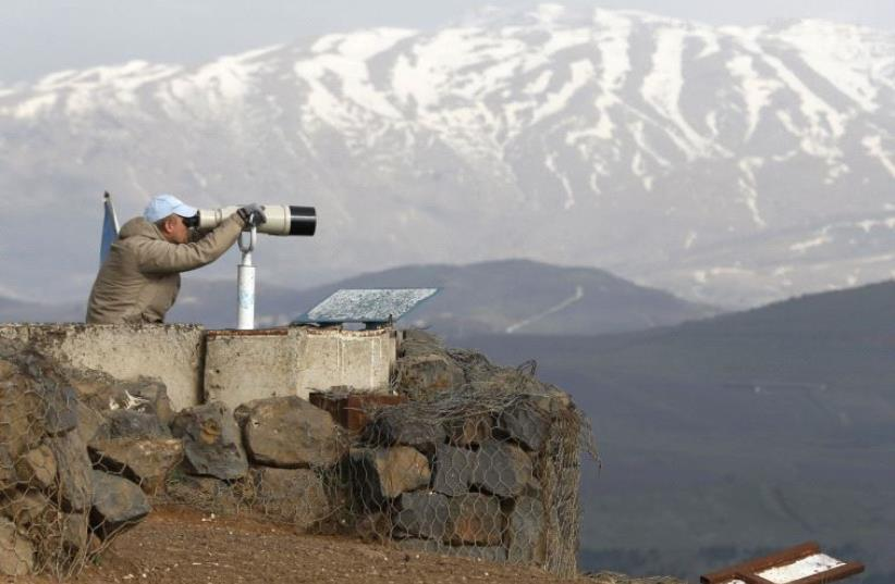 A member of the United Nations Disengagement Observer Force (UNDOF) looks through binoculars at Mount Bental, an observation post in the Israeli Golan Heights (photo credit: REUTERS)