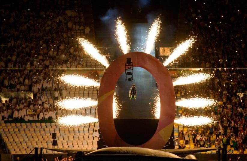 Aaron Wheelz, an extreme wheelchair athlete, goes down a MegaRamp and tears through the panel marking the start of the Opening Ceremony of the Rio 2016 Paralympic Games at the Maracana Stadium in, Rio de Janeiro, Brazil (photo credit: BOB MARTIN FOR OIS / OIS/IOC / AFP)