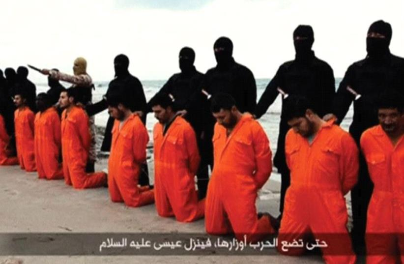 ISIS TERRORISTS pose on a Libyan beach in February 2015 with 21 captured Egyptian Christians they are about to behead (photo credit: REUTERS)