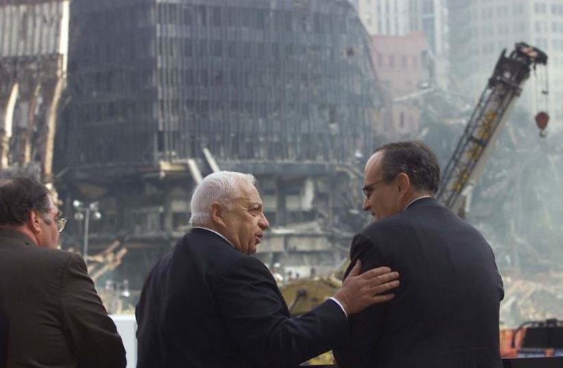Israeli Prime Minister Ariel Sharon talks with New York City Mayor Rudy Giuliani as they look out over the wreckage of the World Trade Center attacks site in 2001, in New York.  (photo credit: REUTERS)
