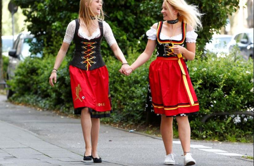 Models pose in the street wearing traditional Bavarian dresses known as a Dirndl, in the national colours of Germany for Euro 2016, in Munich, Germany, June 10, 2016. (photo credit: REUTERS/MICHAELA REHLE)