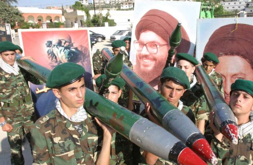 Hezbollah members carry mock rockets next to a poster of the group's leader Sayyed Hassan Nasrallah [FIle] (photo credit: REUTERS)