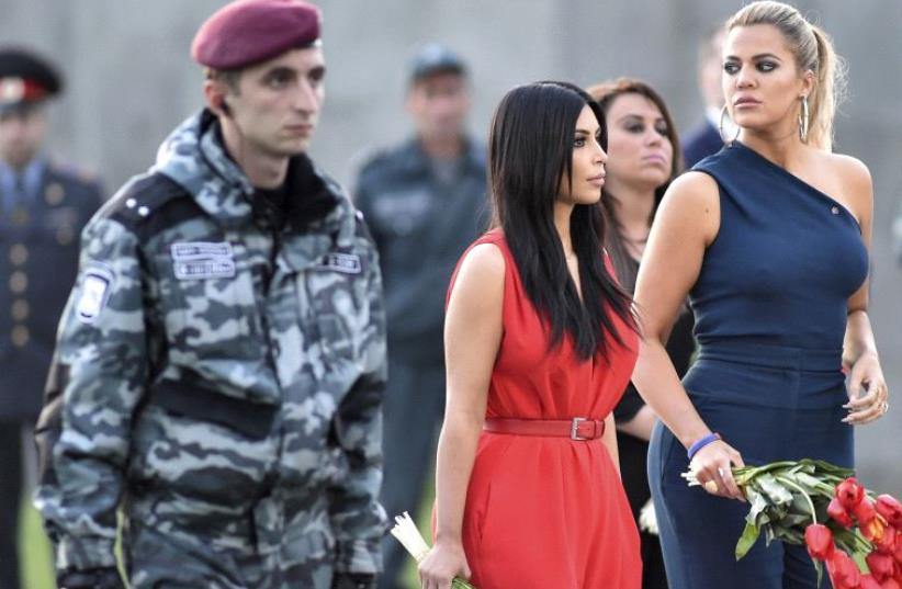 US television personality Kim Kardashian (C) and her sister Khloe Kardashian attend a flower laying ceremony at the Tsitsernakaberd Armenian Genocide Memorial Museum in Yerevan (photo credit: REUTERS)