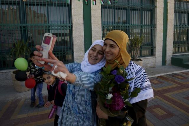 A Palestinian student takes a selfie with teacher Hanan Al Hroub, who is shortlisted to win the Global Teacher Prize, in the West Bank city of Ramallah February 17, 2016.  (photo credit: REUTERS)