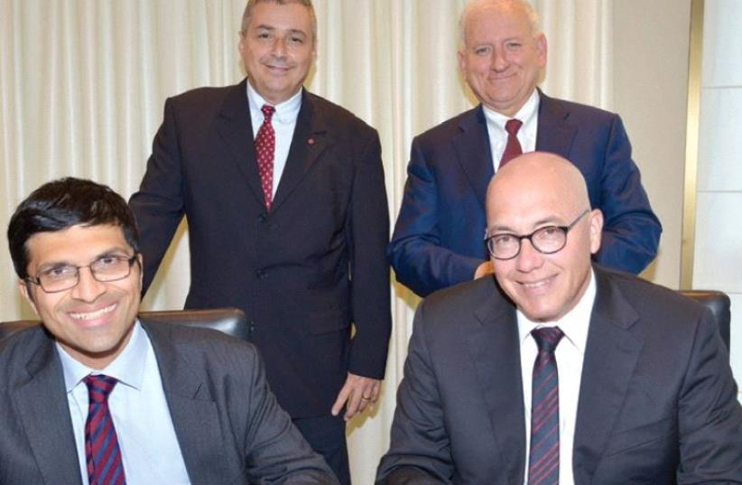 AVI KOCHBA (right), head of innovation at Bank Hapoalim, and Nikhil Rathi, CEO of the London Stock Exchange, sign the MoU on Wednesday, as Bank Hapoalim's chairman Yair Serrousi (back right) and CEO Arik Pinto look on. (photo credit: TAMAR MATSAFI)