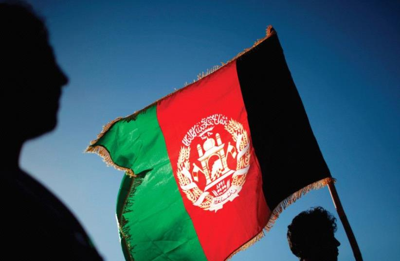 A MAN holds an Afghan flag, one of several that have the words 'God is great' on them (photo credit: REUTERS)