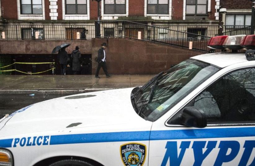 A police vehicle is seen outside a Brooklyn synagogue at the world headquarters of the Chabad-Lubavitch movement in New York City [File] (photo credit: REUTERS)