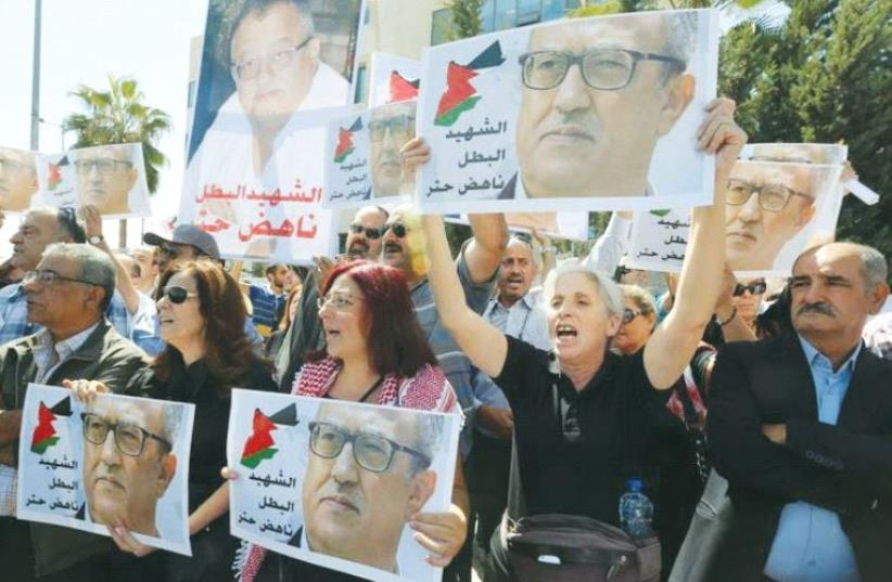 RELATIVES AND ACTIVISTS hold pictures of assassinated Jordanian Christian writer Nahed Hattar yesterday in a protest outside the Prime Minister's Office in Amman, Jordan. (photo credit: MUHAMMAD HAMED/REUTERS)
