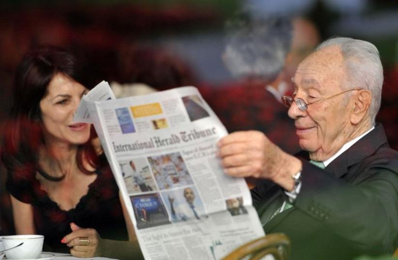 Shimon Peres reads a newspaper during the Ambrosetti workshop in Cernobbio, Italy, September 2012 (photo credit: REUTERS)