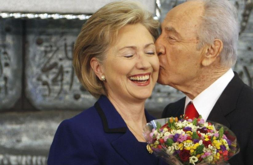 Shimon Peres kisses US Secretary of State Hillary Clinton as he gives her flowers after their meeting in Jerusalem, March 2009 (photo credit: REUTERS)