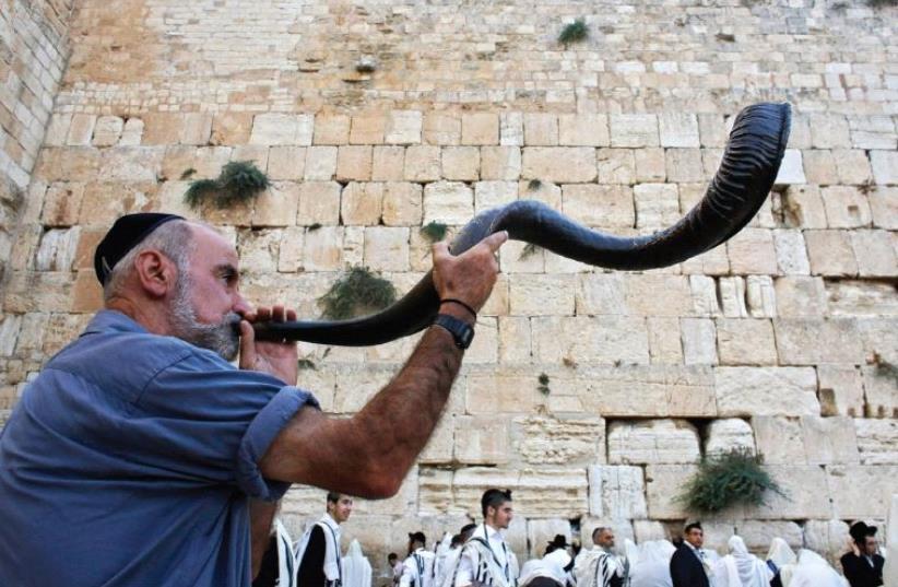 A worshiper blows a shofar at the Western Wall (photo credit: REUTERS)