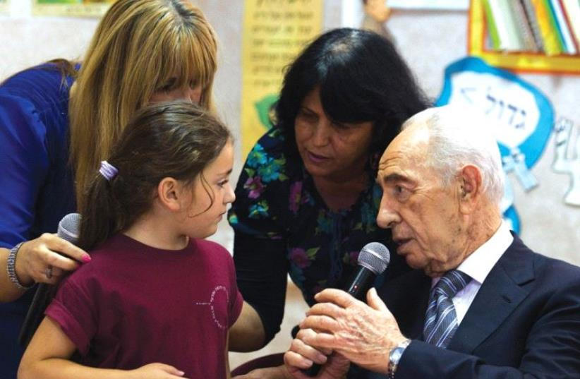 PRESIDENT SHIMON PERES speaks with a first-grader in Sderot. (photo credit: REUTERS)