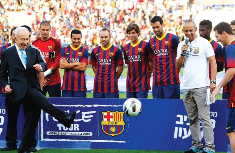 SHIMON PERES kicks a soccer ball to Barcelona superstar Lionel Messi (right) during the Spanish club's 'Peace Tour' trip to Israel in the summer of 2013. (photo credit: REUTERS)