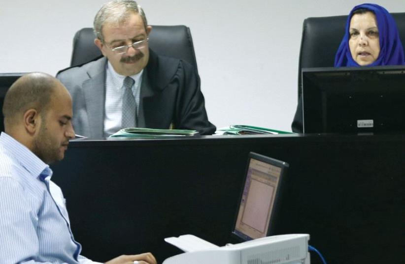 Palestinian judges discuss a petition to suspend municipal elections, at the High Court office in Ramallah on September 8 (photo credit: REUTERS)