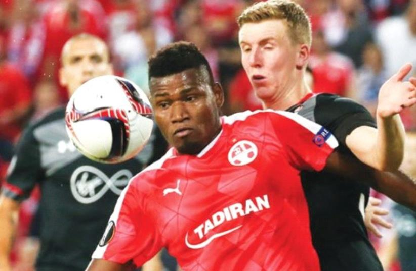 Hapoel Beersheba striker Lucio (front) battles Southampton's Matt Targett during last night's goalless deadlock in Europa League action at Turner Stadium. (photo credit: DANNY MARON)