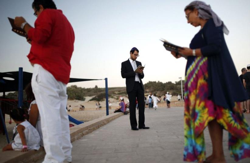 Jews take part in the Tashlich prayer, a Rosh Hashanah ritual, on the shores of the Mediterranean Sea, in the southern city of Ashdod September 5, 2013. During the prayer, bread crumbs are tossed into the waters to symbolically cast away sins. (photo credit: REUTERS)