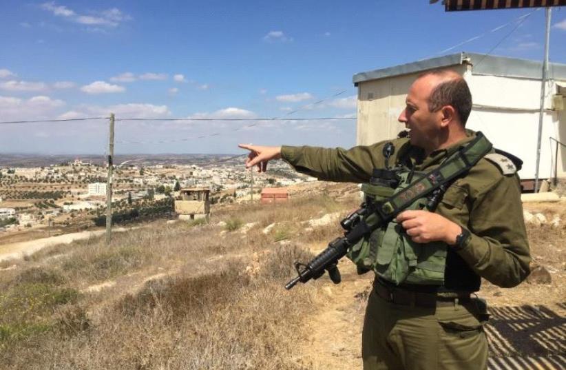 Lt Col Tsafrir Harshoshanim points at Palestinian villages west of Hebron (photo credit: SETH J. FRANTZMAN)