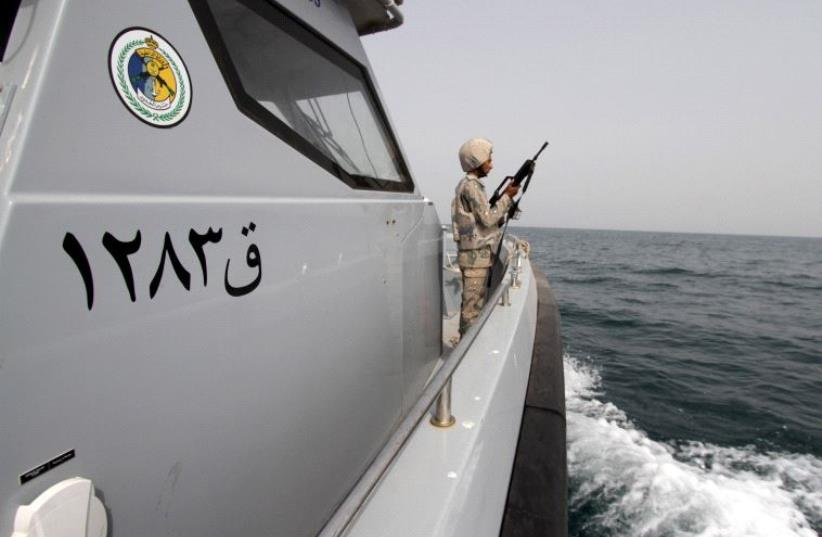 A Saudi border guard watches as he stands in a boat off the coast of the Red Sea on Saudi Arabia's maritime border with Yemen, near Jizan April 8, 2015. (photo credit: REUTERS)