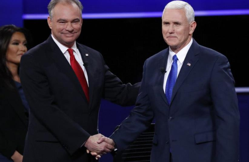 Democratic US vice presidential nominee Senator Tim Kaine shakes hands with Republican US vice presidential nominee Governor Mike Pence (R) (photo credit: REUTERS)