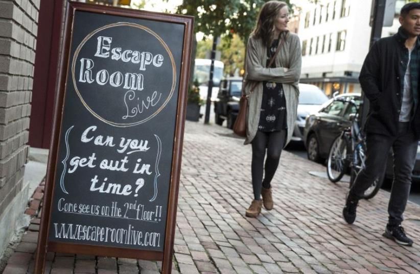 Pedestrians pass the Escape Room Live in Alexandria, Virginia October 17, 2015. (photo credit: REUTERS)