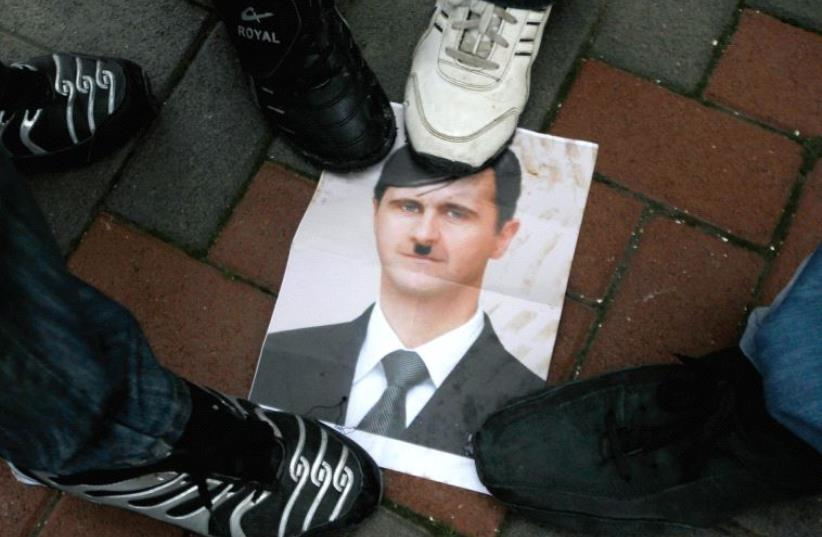 PROTESTERS STEP on a picture depicting Syria's President Bashar al-Assad as Hitler during a protest in the Galilee town of Kfar Kanna in 2012. (photo credit: REUTERS)