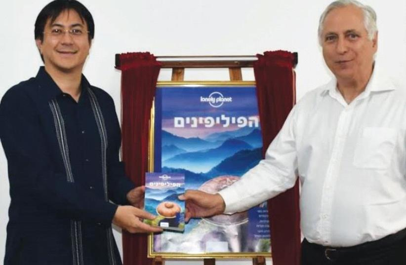 FILIPINO AMBASSADOR Neal Imperial (left) presents a Hebrew edition of the Lonely Planet Philippines guidebook to Boaz Waksman of Ophir Tours. (photo credit: PHILIPPINES EMBASSY)