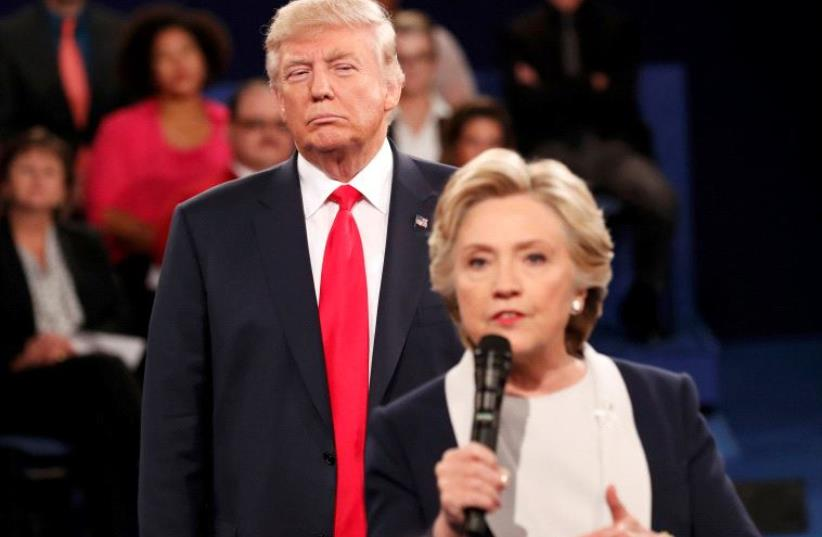 Republican US presidential nominee Donald Trump listens as Democratic nominee Hillary Clinton answers a question from the audience during their presidential town hall debate at Washington University in St. Louis, Missouri, US, October 9, 2016 (photo credit: REUTERS)