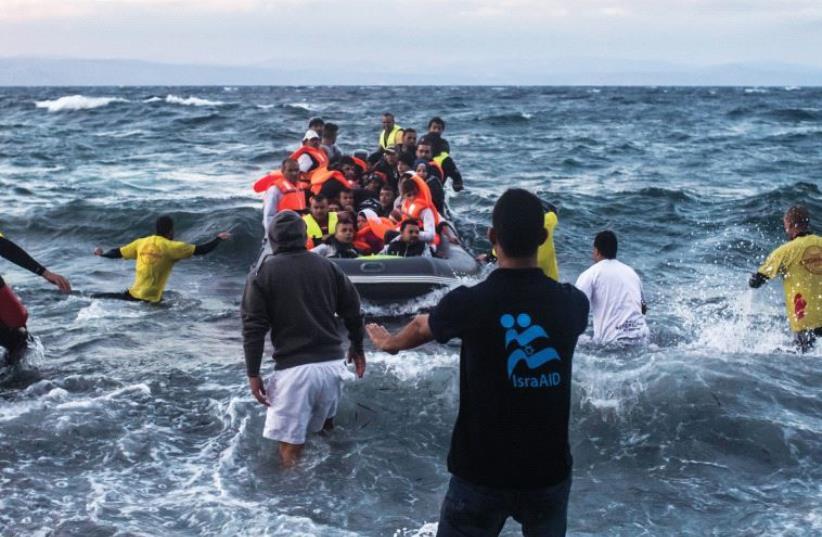 IsraAid workers bring refugees ashore in Lesbos, Greece (photo credit: ISRAAID)