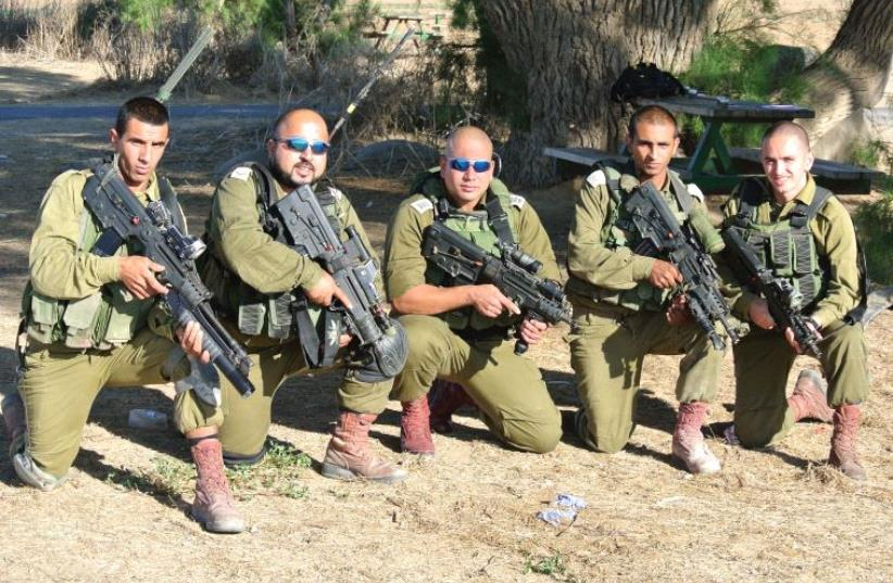 SOLDIERS FROM the Desert Reconnaissance Battalion pose for a group portrait on October 3. They include Muhammad Shibli (second from left), Hussein Fawaze (center) and Roee Hezi (far right). The unit includes Beduin, Jews, Christians, Druse and Circassians. (photo credit: SETH J. FRANTZMAN)