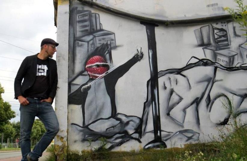 Teacher Christoph Glanz stands next to Palestinian slingshot graffiti.  (photo credit: FACEBOOK)