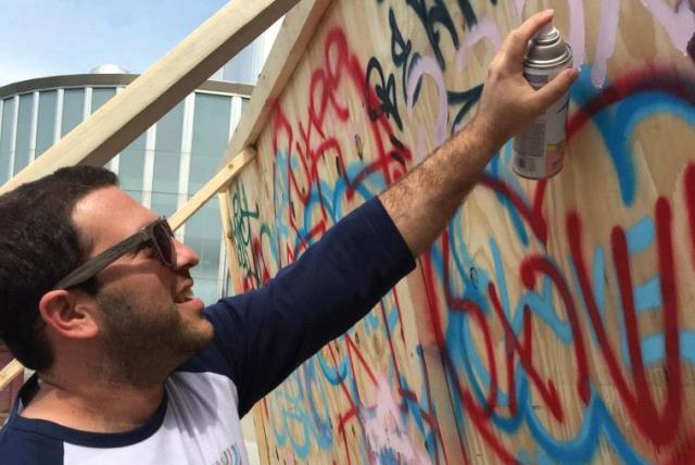 Idan Cohen, a University of Minnesota Hillel Israel Fellow is seen spray painting pro-Israel graffiti on campus (photo credit: Courtesy)
