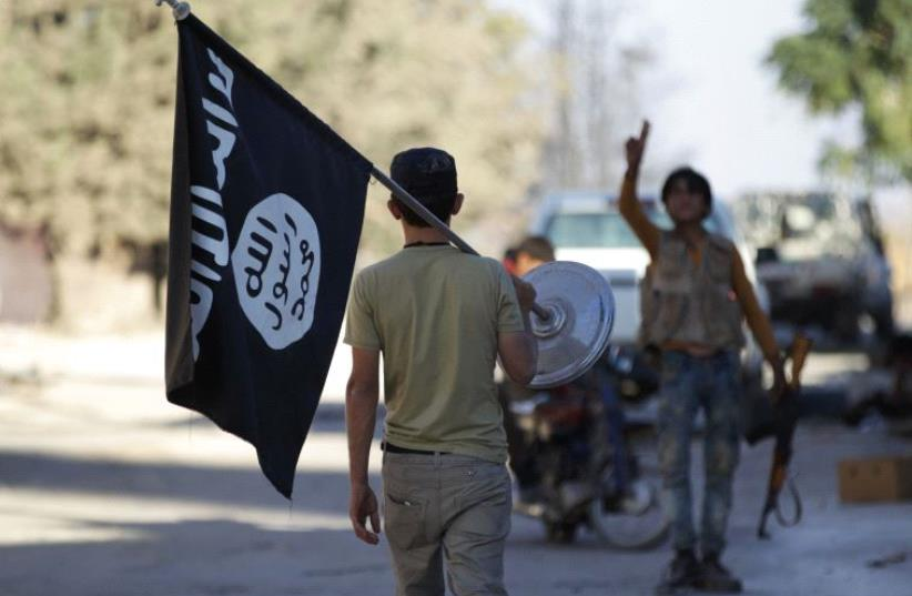 A rebel fighter takes away a flag that belonged to Islamic State militants in Akhtarin village, after rebel fighters advanced in the area, in northern Aleppo Governorate, Syria, October 7, 2016 (photo credit: REUTERS)