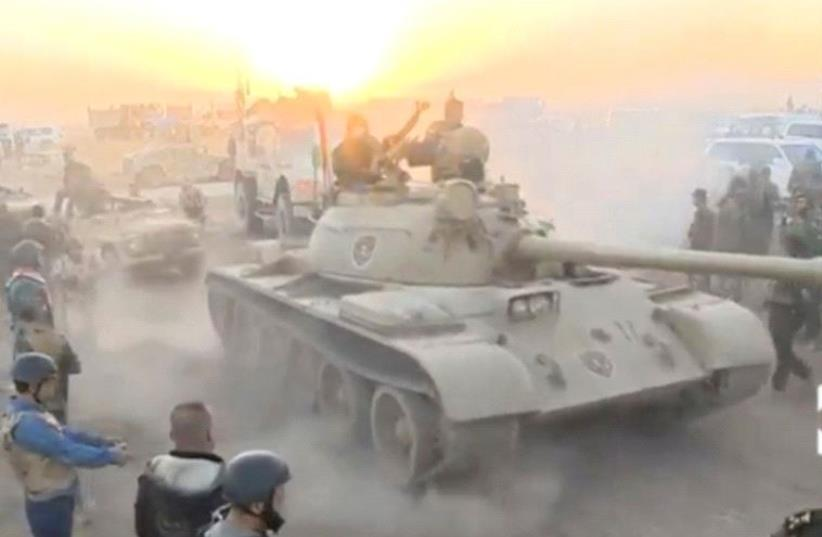 Tanks move past soldiers in military fatigues as the sun begins to set east of Mosul, where the Iraqi government launched a US-backed offensive to drive Islamic State from the northern city, in this still image taken from video released October 17, 2016 (photo credit: REUTERS)
