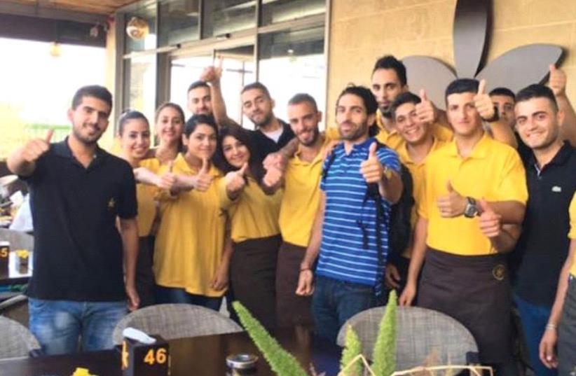 OWNER JOHN SAADEN posing with members of his staff outside Jasmine Cafe in Nablus. (photo credit: FACEBOOK)