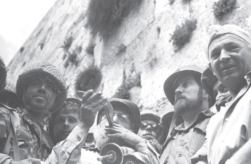 IDF CHIEF RABBI Shlomo Goren blows a shofar while he clutches a Torah scroll at the Western Wall on the day Jerusalem was reunified in June 1967 (photo credit: GPO)