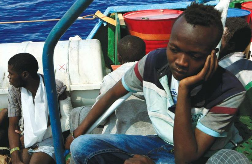 ISSAM IBRAHEEM (right), 13, a migrant from Darfur, sits inside a vessel after he was rescued from an overcrowded dinghy by members of the German NGO Jugend Rettet. The rescue operation took place off the Libyan coast in the Mediterranean Sea last week. (photo credit: REUTERS)