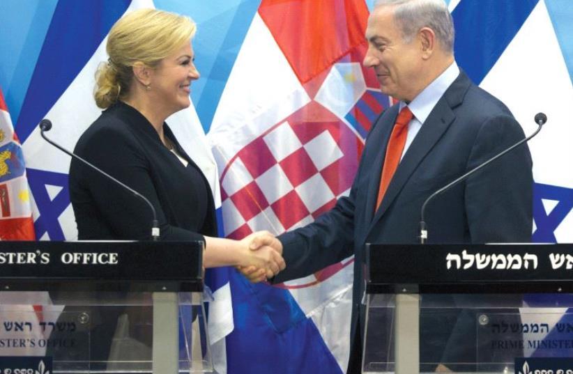 PRIME MINISTER Benjamin Netanyahu and Croatian President Kolinda Grabar-Kitarovic shake hands during their meeting in Jerusalem in 2015. (photo credit: REUTERS/HEIDI LEVINE)