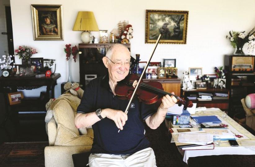 Yonatan Rosen joue sur le violon de sonpère Moshe Rosenzweig, auteur de ces partitions composées en 1945 (photo credit: YAD VASHEM)