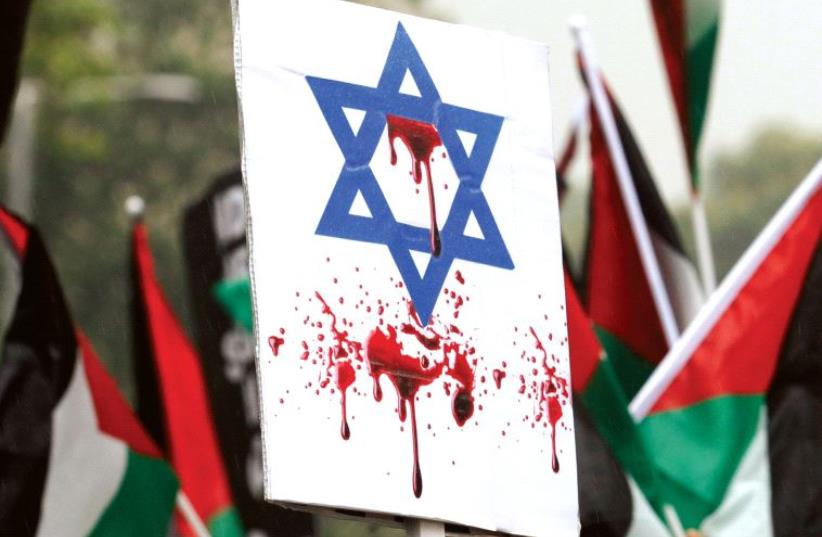AN ISRAELI FLAG stained with fake blood at a pro-Palestinian rally in London. (photo credit: REUTERS)