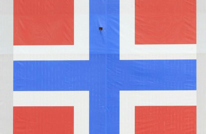 A woman cycles past a banner of the Norwegian flag attached to a warehouse in Oslo, Norway. (photo credit: REUTERS)