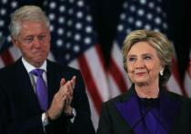 Hillary Clinton, accompanied by her husband former US President Bill Clinton (L)
