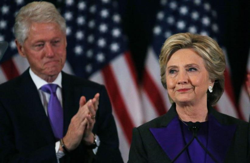 Hillary Clinton, accompanied by her husband former US President Bill Clinton (L), addresses her staff and supporters about the results of the US election. (photo credit: REUTERS)