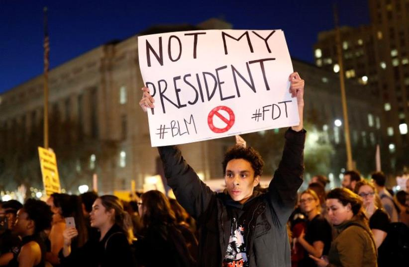 A demonstrator holds a sign during a protest in San Francisco, California, US following the election of Donald Trump as the president of the United States November 9, 2016. (photo credit: REUTERS)