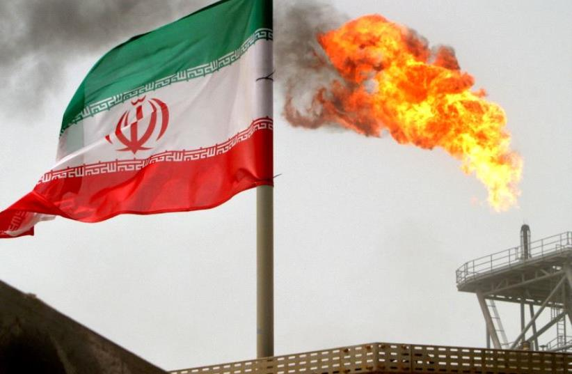 A gas flare on an oil production platform in the Soroush oil fields is seen alongside an Iranian flag in the Persian Gulf, Iran, July 25, 2005. (photo credit: REUTERS)