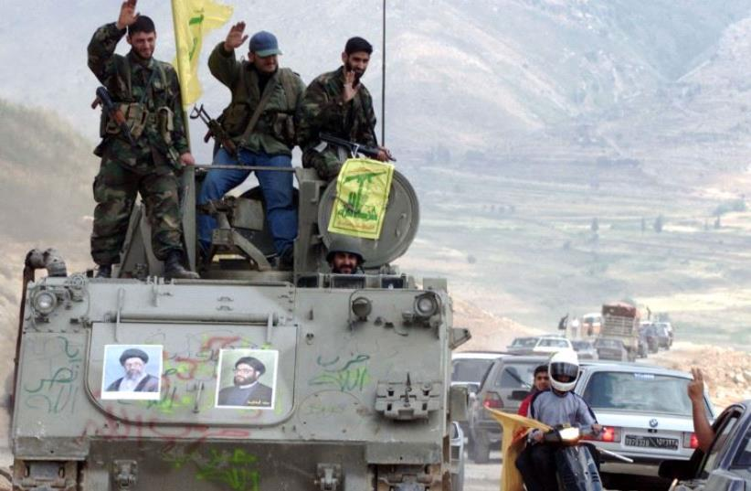 Pro-Iranian Hezbollah guerrillas, riding on an APC M113 used by pro-Israeli militiamen, wave to passing motorists as they drive in the former Israeli security zone in the Tell Nahas area of south Lebanon May 26, 2000.  (photo credit: REUTERS)