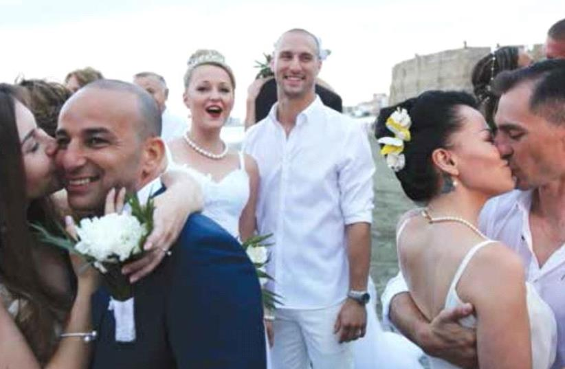 Couples of Russian and Israeli origins kiss during a mass wedding in Larnaca, Cyprus, in June last year (photo credit: REUTERS)