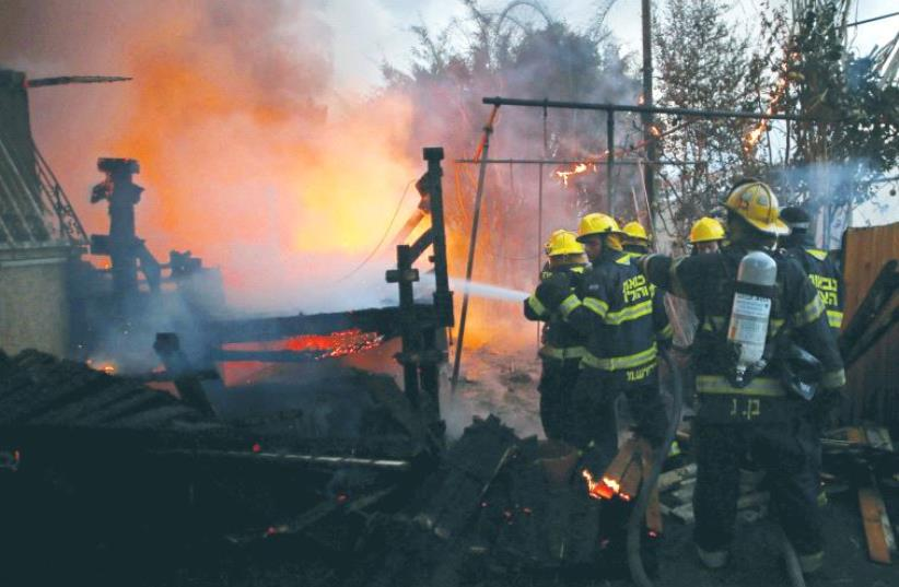 Fire-fighters work to extinguish a fire in Haifa. (photo credit: REUTERS)