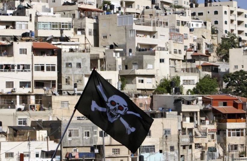 Protesters against Jewish settlement activity in the Silwan neighbourhood, outside the old city in Jerusalem hold a skull and bones flag (photo credit: REUTERS)