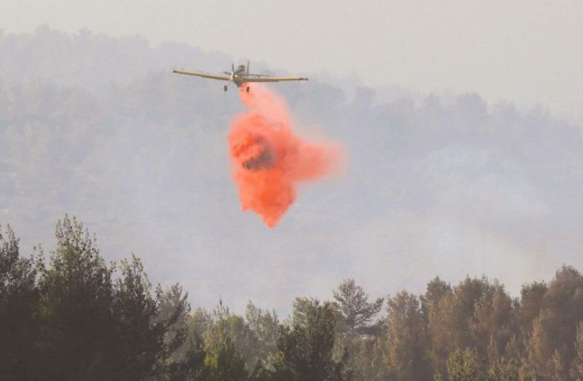 A PLANE combats forest fires in the Jerusalem area last week (photo credit: REUTERS)